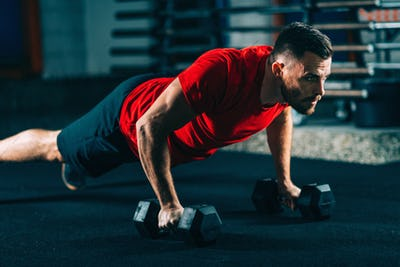 Cross training. Young man exercising with dumbbells