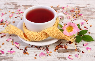 Cup of tea with wild rose flower on old rustic board