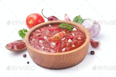 tomato sauce in gravy boat on white