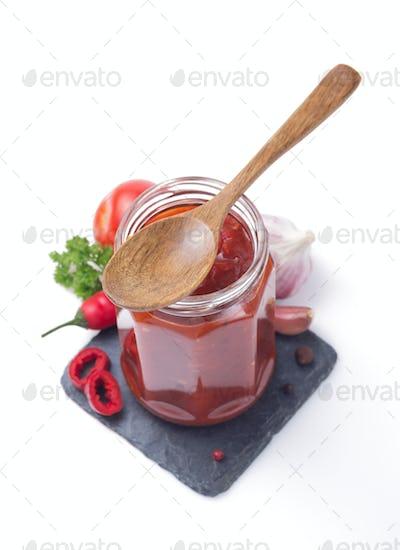 tomato sauce in glass jar on white