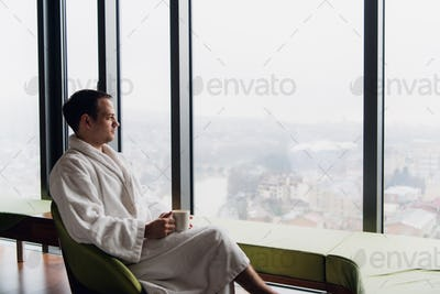 young man enjoying evening coffee and beautiful sunset landscape of the city while standing by the