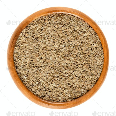 Carrot seeds in wooden bowl over white