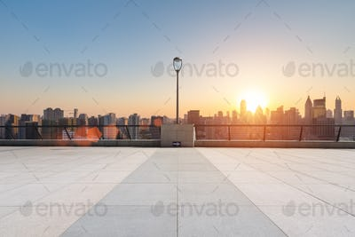 empty floor in sunset with skyline and buildings