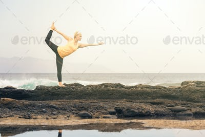 Yoga girl meditating and relaxing in yoga pose, ocean view