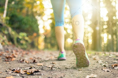Woman walking and hiking in autumn woods