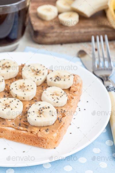 vHealthy breakfast sandwich with crunchy peanut butter, banana a