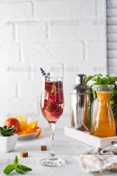 Refreshing cocktail with champagne and cranberry with ice, ginger and lavender on wooden background