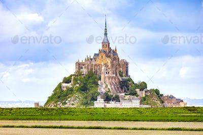 Mont Saint Michel monastery landmark and green field. Normandy,