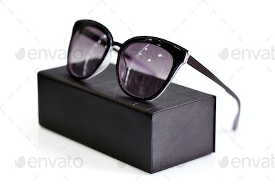 Fashionable sunglasses with box on white background