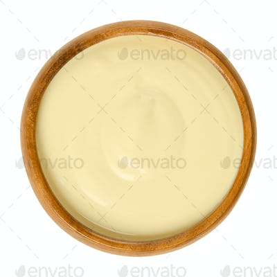 Sauce Hollandaise in wooden bowl over white