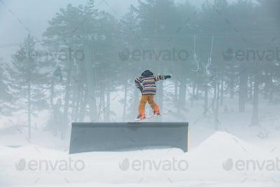 Skier doing snowboarding jumping a ramp