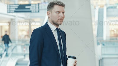 Young businessman in suit with coffee