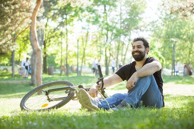 Bearded man next to his bicycle resting on the ground
