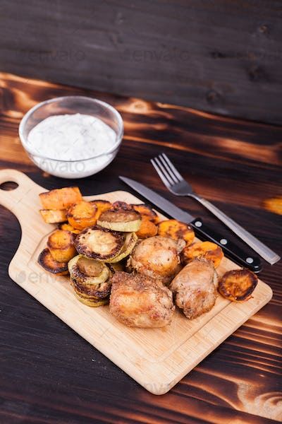 Grilled chicken next to fried zucchini and sweet potatoes