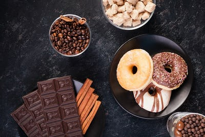 Top view of chocolate tablets, donuts, brown sugar with peanuts in chocolate and coffee beans
