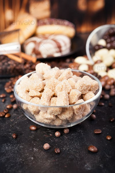 Brown sugar in a glass bowl next to candies and sweets