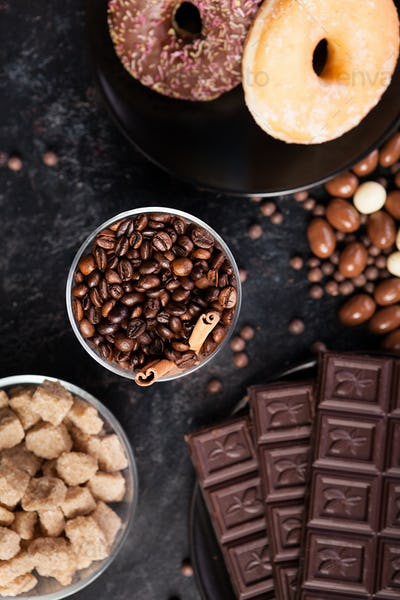 Coffee beans in a glass with cinnamon sticks next to different types of candies
