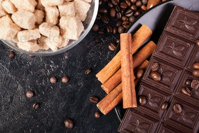 Top view of brown sugar, chocolate tablets and cinnamon sticks