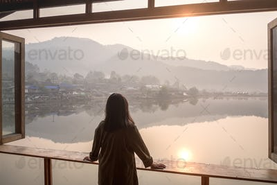 Girl looking out at lake in the morning