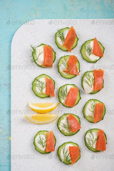 Cucumber canapee with cottage cheese and salmon.