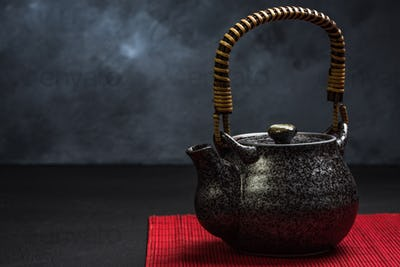 Traditional Tea pot on red bamboo