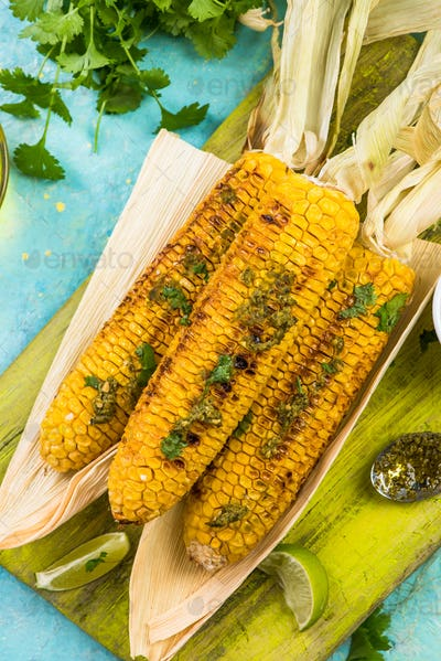 Serving grilled corn in husk with pesto and lime and herbs