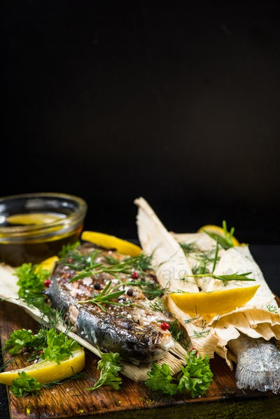 Fish grilled and served in corn husk with herbs