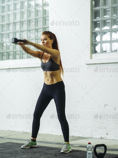 Beautiful young redhead exercising with a kettlebell