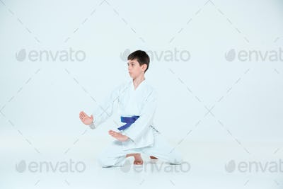 The boy posing at Aikido training in martial arts school. Healthy lifestyle and sports concept