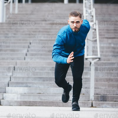 Handsome sportsman running in athletic clothes