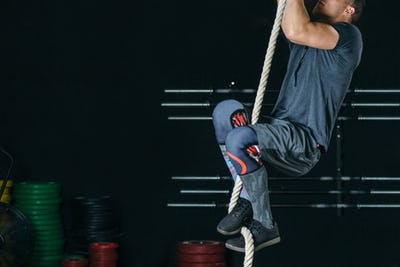 Man doing rope climb exercise