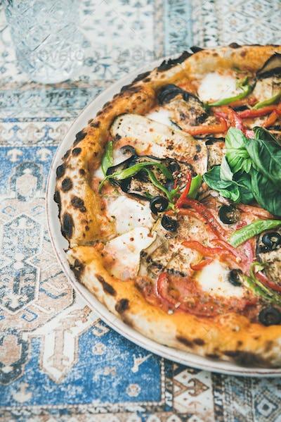 Freshly baked vegetarian pizza over oriental tile background