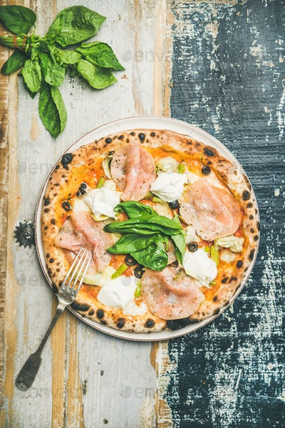 Freshly baked pizza with ham, artichokes, cheese, basil on plate