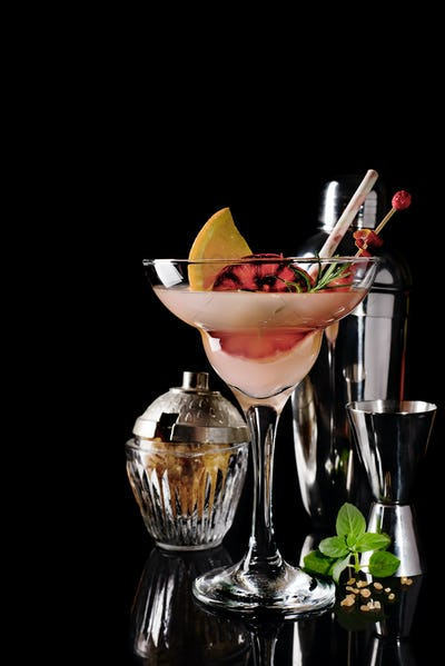 Refreshing alcoholic cocktail margarita with citrus fruits on black glass background