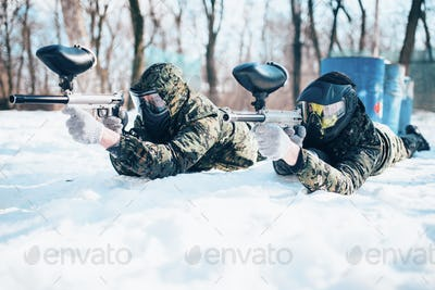 Two paintball players lies on the snow