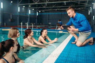 Female fitness class with trainer, aqua aerobics