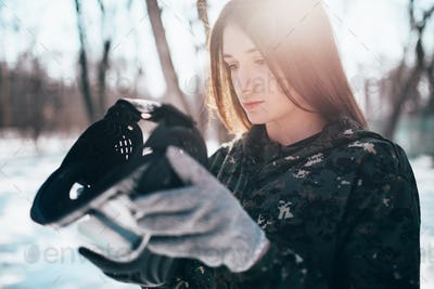 Female paintball player puts on protection mask