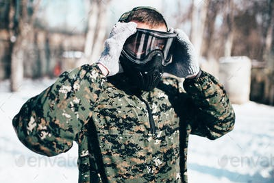Male paintball player puts on protection mask