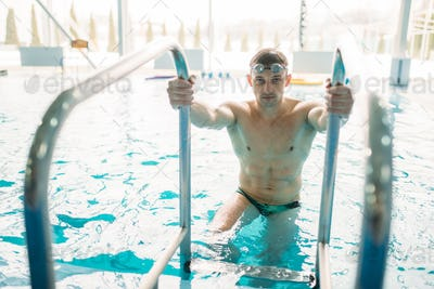 Swimmer in goggles climbs out of swimming pool