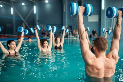 Class with trainer on workout with aqua dumbbells