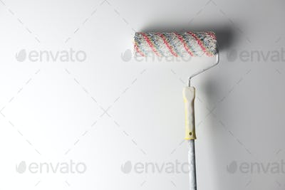Painting roller on white wall background