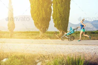 Running mother with stroller enjoying motherhood at sunset lands