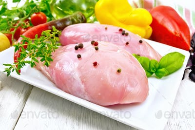 Chicken breast raw in plate with vegetables on table