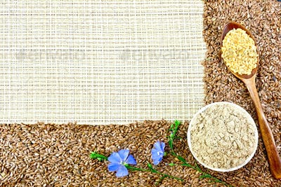 Flour and flax seeds with flowers on coarse woven fabric