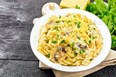 Fusilli with mushrooms and cream in plate on board