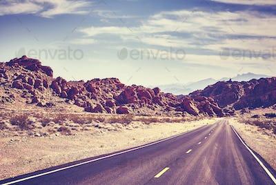 Retro toned desert road, travel concept.