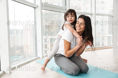 Photo of caucasian young woman and her girl kid playing around,