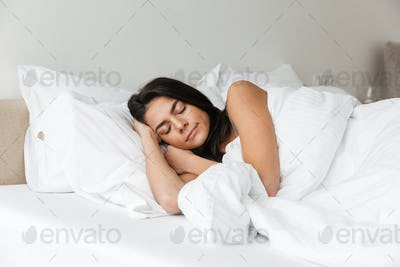 Portrait of brunette woman sleeping at home in bed on pillow, wi