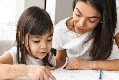 Image of lovely mother and little daughter enjoying painting tog
