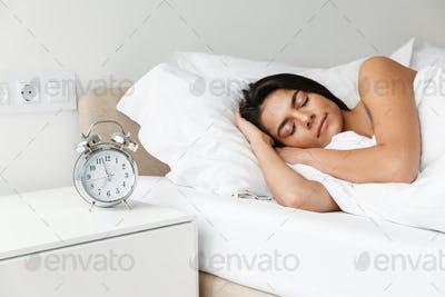 Portrait of beautiful young woman sleeping in bed at bedroom, wi